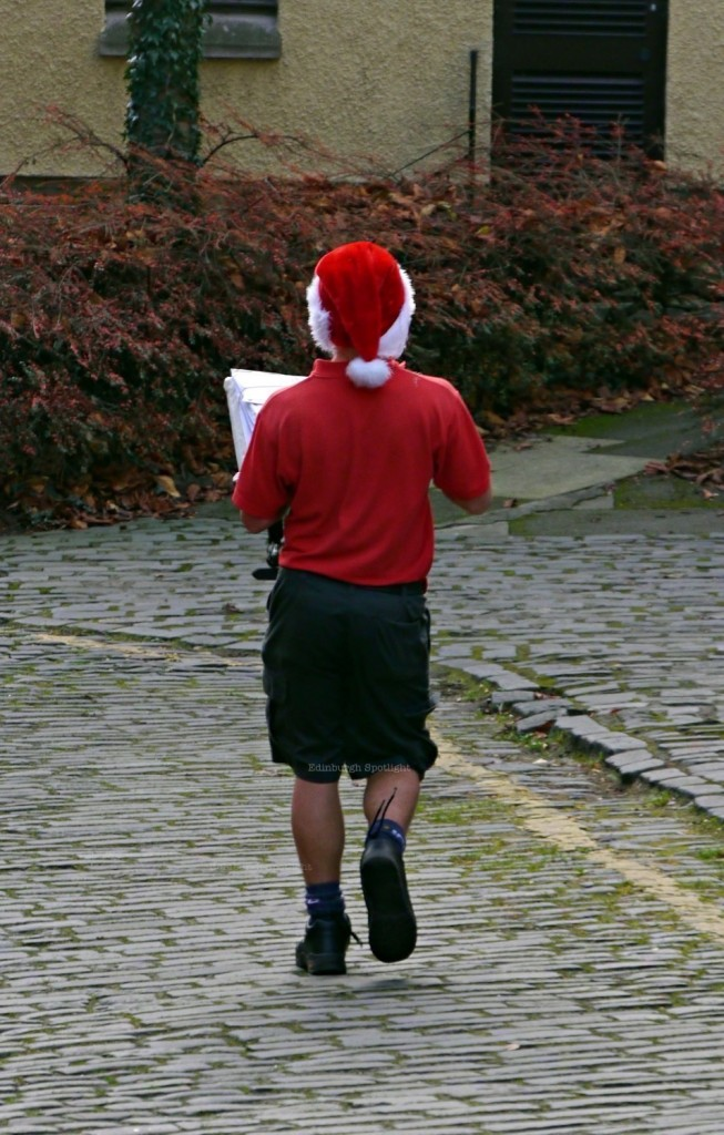 A postie wearing shorts in December and his santa hat!